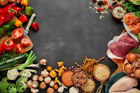 コピースペースで暗い素朴な灰色の背景に、健康、有機、古収穫物、豆類、肉や野菜の品揃え。 写真素材