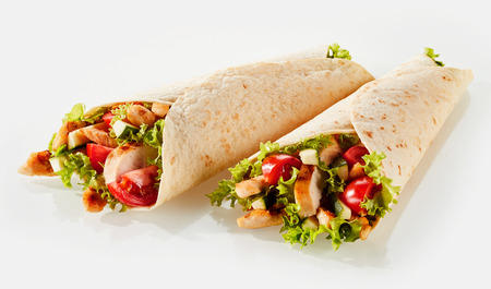 Two fresh tortilla wraps with vegetable filling and chicken against white background