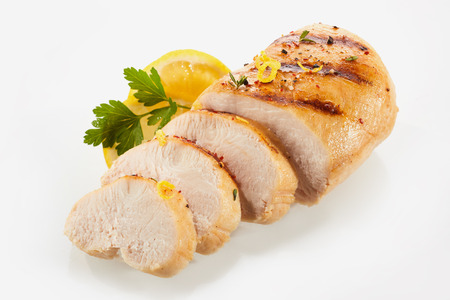A close up of a golden, grilled, sliced chicken breast with lemon seasoning, garnish and a white background and copy space.