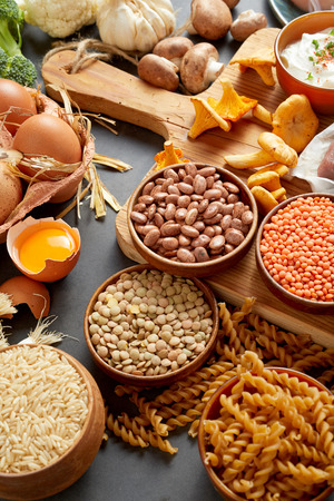An authentic assortment of healthy, organic legumes, eggs, pasta, mushrooms and meat on a rustic table setting with a wooden chopping board in vertical portrait orientation.
