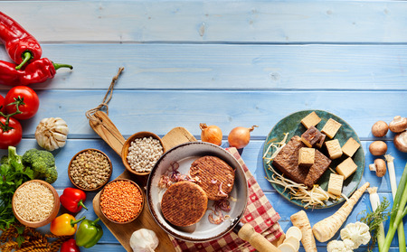 A rustic and authentic assortment of vegetarian foods including veggie burger patties, tofu and various legumes and vegetables on a stained, blue timber table background and wooden chopping board.