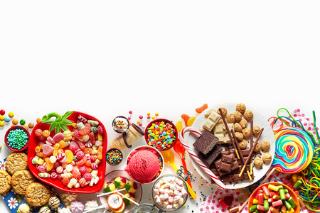 Large colorful selection of kids party food and sweets with cookies, ice cream, lollipops and candy isolated on white as a lower border with copy space Imagens