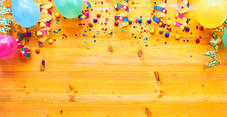 Carnival or party background border with colorful balloons and confetti on wood with copy space in a wide angle view