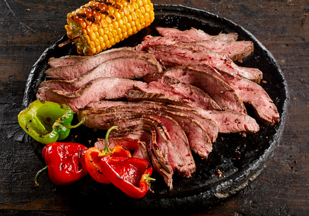 Grilled tender medium rare flank steak thinly sliced and served with roast corn on the cob and sweet peppers on a plate