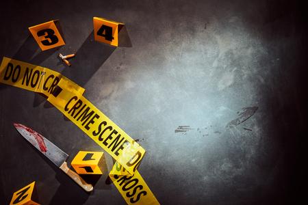 黄色テープで警察犯罪現場と横のコピー スペースと番号の手がかりで血まみれのナイフとタバコ スタブ