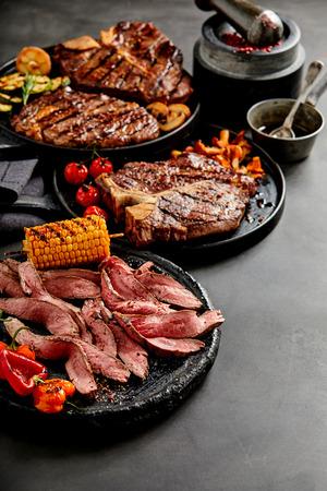 I piatti e le verdure cucinate cotti in padelle con condimenti e mirtilli su uno sfondo scuro in stile verticale