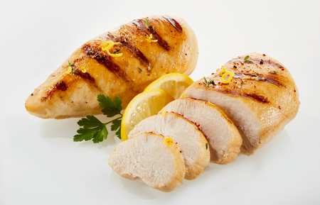 Pieces of roasted chicken cut in slices with lemon and parsley against white background 版權商用圖片