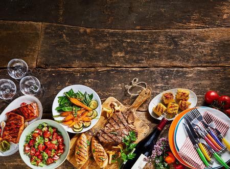 素朴な木製のベンチの背景に、肉料理、野菜、ワイン、ダイニング食器をグルメ。