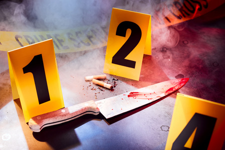 Bloody knife and cigarettes marked with numbers at crime scene