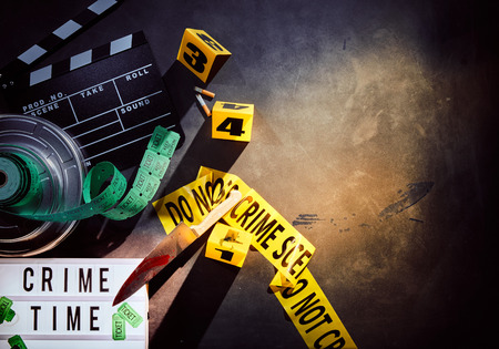 White sign titled crime time next to film reel and yellow crime scene tape with black and rolls of tickets