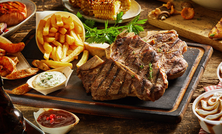 Grilled meat with french fries, vegetables and dips served on wooden board Stock Photo
