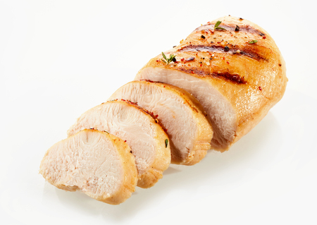 A close up of a golden, grilled, sliced chicken breast with a white background and copy space.