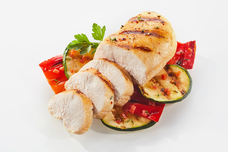 Elevated view of cooked and sliced chicken with courgettes and parsley on studio background Stock Photo