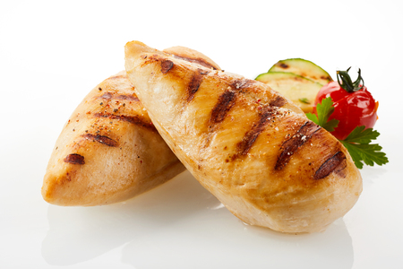 A close up of a gourmet dish with grilled chicken breast and vegetables on a white background with copy space.