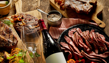 Authentic cooked meats and fine dining crockery with wine bottle, glasses and chopping boards on a rustic timber bench top.