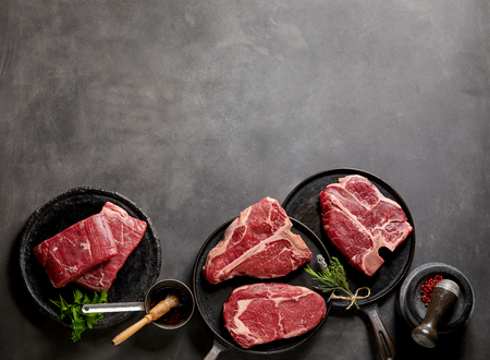 Raw steaks and frying pans with seasoning, garnishes and ingredients on a dark rustic background with copy space.