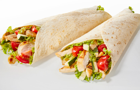 Two chicken and salad wraps on studio background Imagens