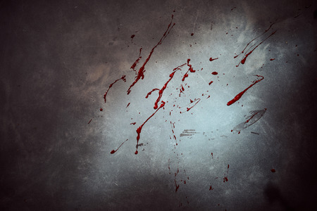 Blood splatter on a cement wall or floor at a crime scene with heavy vignetting or highlighted by a torch