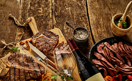Authentic, gourmet cooked meats and fine dining crockery with wine bottle, glasses and chopping boards on a rustic timber bench top. Stock fotó