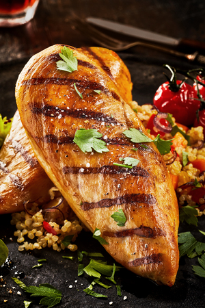 Grilled chicken breast served with parsley, couscous and tomatoes