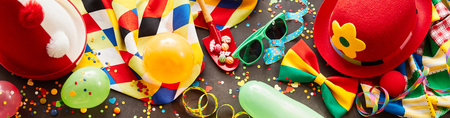 Colorful carnival banner with party accessories including hats, glasses, balloons, streamers and bow ties in a full frame view,