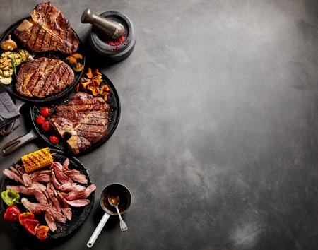 Gastronomische gekookt vlees en groenten in koekenpannen met kruiden en garneert op een donkere achtergrond met kopie ruimte.