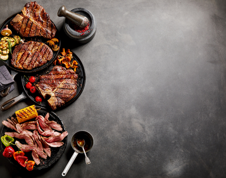 Gourmet cooked meats and vegetables in frying pans with seasoning and garnishes on a dark background with copy space. Stock Photo