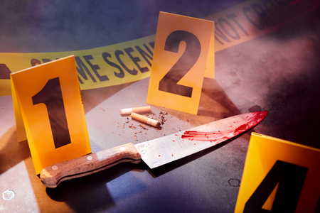 Bloody knife and cigarettes marked with markers at crime scene Stock Photo