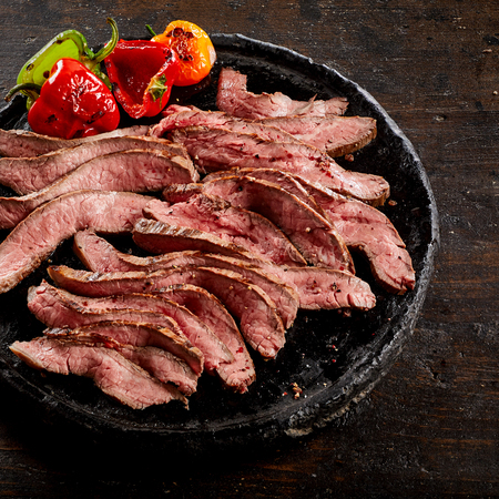 Old blackened plate with sliced medium rare grilled flank steak served with roast tomato and sweet peppers in a square format Stock Photo