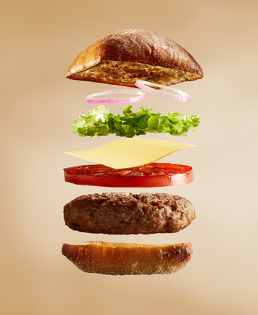 An exploded diagram view of a burger, with onion, lettuce, cheese, tomato and a toasted bun on a plain background with copy space.