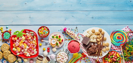An assortment of colourful, festive sweets, ice-cream and candy on a timber table with copy space.