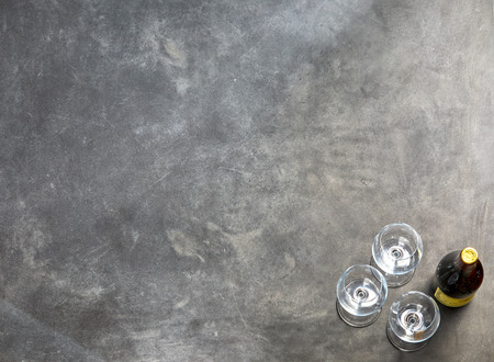 High angle view of wine bottle with three empty glasses standing on dark background Stock Photo