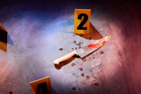 Bloody knife and blood stains marked with evidence number markers at crime scene