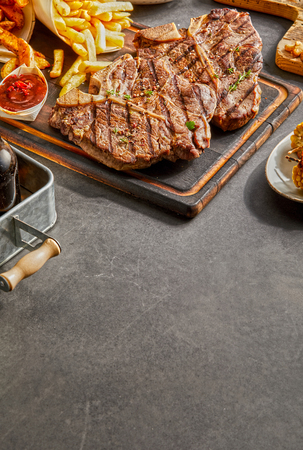 Serving of grilled t-bone and porterhouse steaks with French fries and a ketchup dip with copy space in the foreground on grey slate Stock Photo