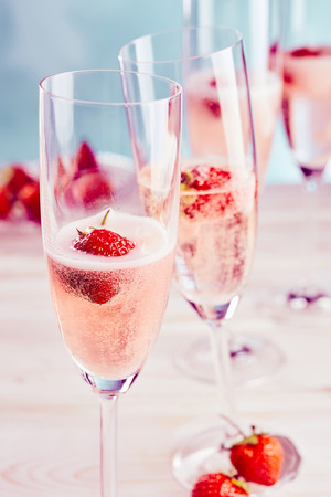 Delicious sparkling pink champagne with fresh strawberries served in stylish flutes for a romantic celebration or special occasion Фото со стока - 86034629