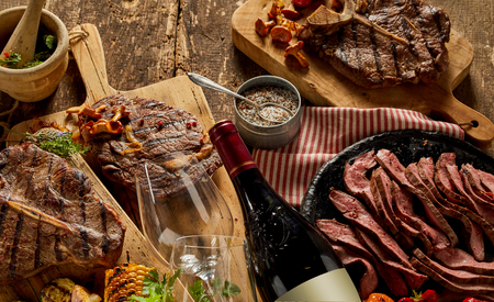 Authentic, gourmet cooked meats and fine dining crockery with wine bottle, glasses and chopping boards on a rustic timber bench top. Zdjęcie Seryjne