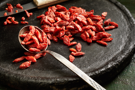 Healthy dried goji berries on an old wooden board with small silver spoon in a close up view