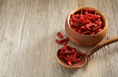 Dried red goji berries in a wooden bowl classes as a superfood for their high level of antioxidants, vitamins and nutrients viewed high angle on a table with copy space