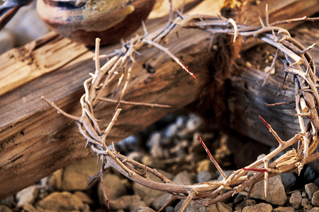 Bloodstained crown of thorns on a wooden cross conceptual of the suffering, martyrdom, crucifixion and resurrection of Christ at Easter Фото со стока