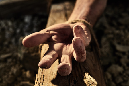 Bloodied hand with nail hole on a wooden cross conceptual of the martyrdom and crucifixion of Christ and his resurrection during Easter Фото со стока