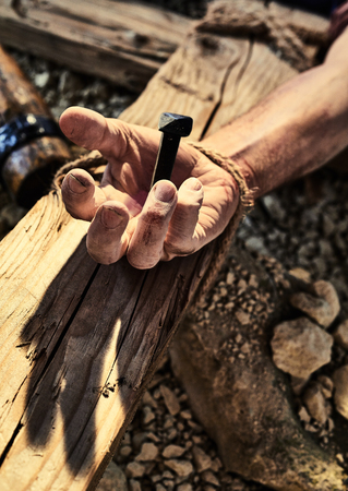 Reenactment of Jesus Christ crucifixion with human hand nailed to wooden cross in close up