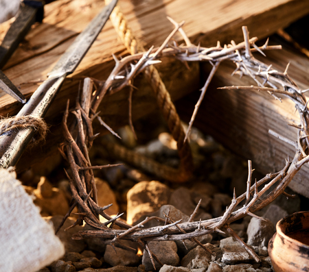 Crown of thorns against wooden cross with spear among crucifixion symbols