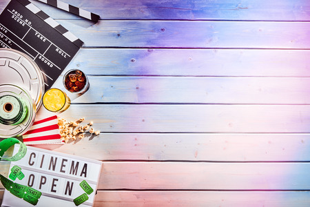 Multiple film reels and ticket rolls next to tipped over popcorn and two cups of liquid over wood panel background Banco de Imagens - 86801331