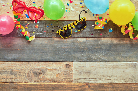 Colorful border of carnival or party accessories on a natural wood background with copy space