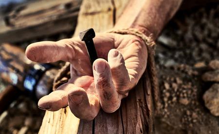 Hand des Christus nagelte zum Kreuz mit einer nahen hohen Ansicht der Hand eines Mannes mit einem Eisennagel durch, der auf ein hölzernes Kreuz gehämmert wurde, das von der Kreuzigung von Christ zu Ostern symbolisch ist Standard-Bild