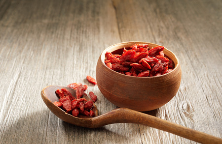 Bowl of healthy organic dried goji berries high in antioxidants, vitamins and nutrients eaten for their medicinal qualities on a wooden table viewed close up low angle