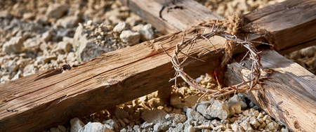 Easter banner commemorating the Crucifixion with a close up view of a wooden cross on stony ground with a bloodstained crown of thorns