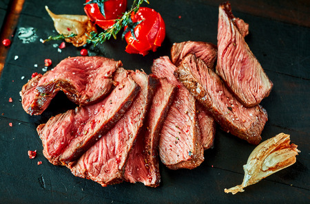 Slices of roast beef with tomatoes against wooden board Stock Photo