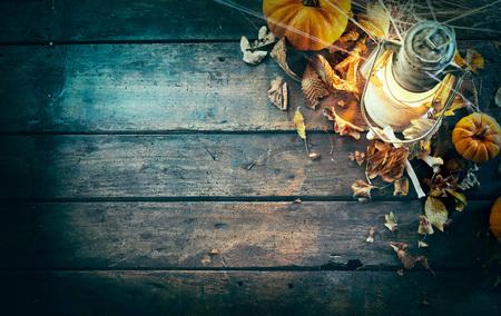High angle view of pumpkins, bones, vintage lamp under spider web against wooden background