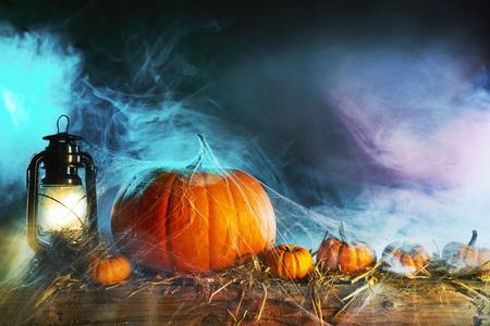 Halloween theme with pumpkins under spider web with vintage lamp against smoky dark background Foto de archivo